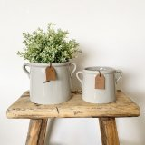 A stylish grey ceramic pot planter with small eared handles. Complete with a tan coloured PU leather slogan tag.