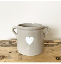 A rustic pot with a heart shaped design. Complete with twin handles.