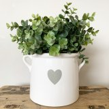 A beautifully simple white ceramic pot with a grey heart design and twin handles.