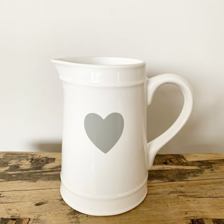 A classic white ceramic jug with a grey heart detail. A simple living interior item.