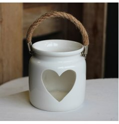 A rustic ceramic lantern with a white finish. Complete with a heart cut out design and chunky rope handle.