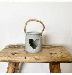 A rustic grey lantern with a heart detail and chunky rope handle.