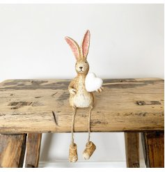 A charming shelf sitting rabbit ornament with a chic white heart decoration.