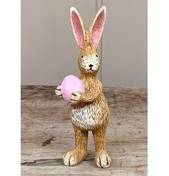 A rustic standing rabbit decoration, complete with tall ears and a pretty pink polka dot egg.