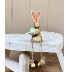 A unique shelf sitting rabbit decoration, complete with pointed ears, a green dotty egg and rustic dangling legs.