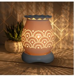 A chic aroma lamp with a pretty scalloped dish and an attractive arch design.