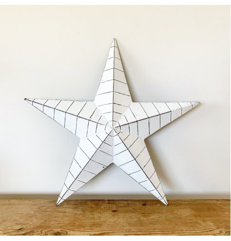 A vintage inspired white and black metal barn star with ridges and a distressed finish.