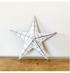 A rustic white metal barn star with black ridges and a distressed finish.
