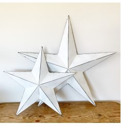 A vintage inspired white metal barn star with a distressed finish and hook to hang.