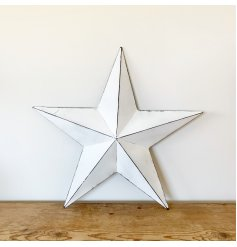 A rustic white metal barn star with a distressed finish.