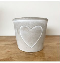 A beautiful grey cement planter with a heart outline design. Complete with white painted detailing.