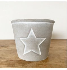 A rustic cement planter with a distressed painted finish and star design.