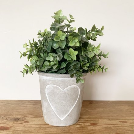 A rustic grey and white pot planter with an embossed heart design.