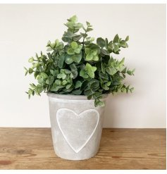 A chic and contemporary cement pot planter with a painted heart design.