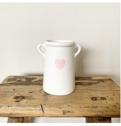 A pretty vase with small handles and a pink heart shaped design.