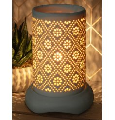 A sleek white toned ceramic aroma lamp set with an intricate cut detail