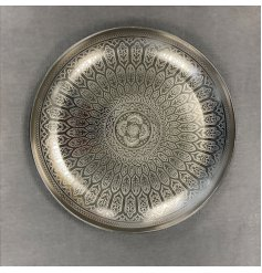 A large round iron based bowl set with a beautifully intricate etched pattern decal