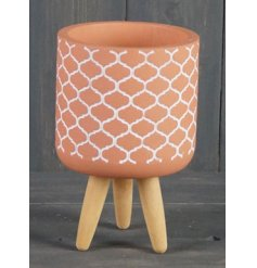 Perfect for all those indoor plants! A terracotta pot with an added embossed decal and wooden pin legs