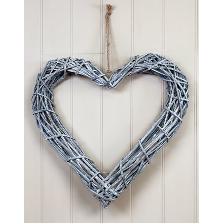 A rustic rattan heart wreath with a woven design and chunky jute rope hanger.