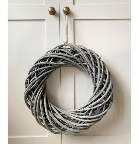 A small woven rattan wreath decorated with a subtle white washed tone and set with a chunky rope hanger