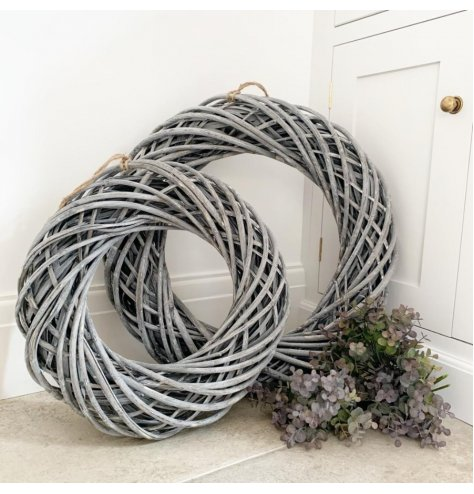 A large woven rattan wreath decorated with a subtle white washed tone and set with a chunky rope hanger