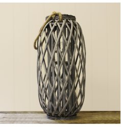A tall grey woven lantern for a candle