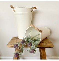 A tall metal bucket in cream with twin chunky rope handles.