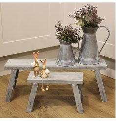 A set of 2 rustic wooden potting benches with a washed, distressed finish.