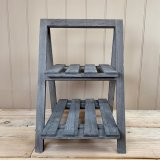 A natural wooden 2 tiered Display Shelf featuring an overly distressed grey washed tone