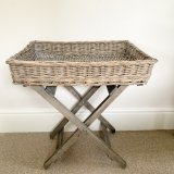 A rustic wicker tray table with a grey washed distressed finish.