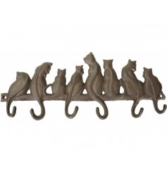 A charming cast iron wall hook with an assortment of sitting cats with curled tails.