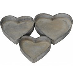 A set of 3 rustic metal heart shaped trays. Each has a raised rim for decoration and easy storage.
