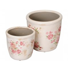 A set of 2 rustic cream planters, each with a pretty pink rose design.