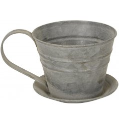 A rustic metal teacup planter with saucer. A unique gift item and garden pot/planter.