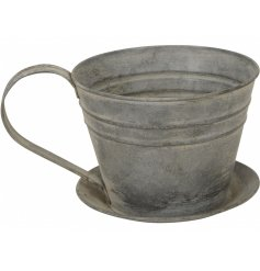 An overly distressed metal planter in a Teacup and Saucer shape