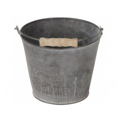 A stunning wild garden bucket planter with wooden handle and washed finish.