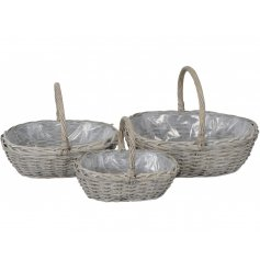 An assorted sized set of woven wicker basket shaped planters complete with added handles and a plastic inner lining