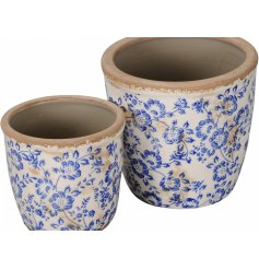 A set of 2 vintage inspired floral blue planters. Each has a distressed aesthetic