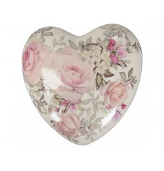 A beautiful heart shaped decorative ornament with a pretty rose design.