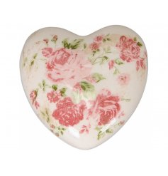 A shabby chic heart shaped ornament with a pink floral design.