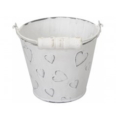 A shabby chic style metal bucket with embossed hearts and a distressed finish. Complete with wooden handle.