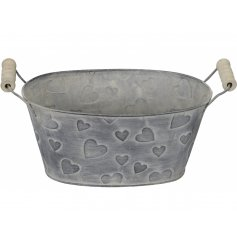 A rustic living metal planter with embossed hearts and a white washed finish. Complete with wooden carry handles.