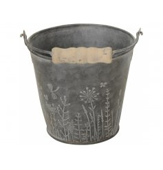 A beautiful grey metal bucket planter with an intricate wild garden floral design.
