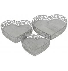 A set of 3 unique metal storage trays. Each heart shaped tray has an intricate floral design and washed finish.