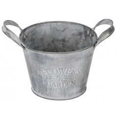 A rustic metal planter with a grey washed finish. Complete with an attractive flowers and garden slogan and handles.