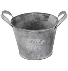 A distressed grey zinc bucket with an attractive Flowers and Garden slogan.