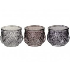 An assortment of 3 pink and purple tonal glass t-light holders. Each has a vintage inspired floral, cut glass design.
