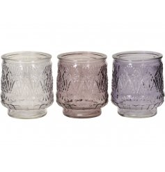 A mix of glass candle holders in purple, pink and clear hues. Each is beautifully decorated