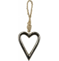 A rough luxe silver hanging heart decoration, styled with a chunky rope hanger.