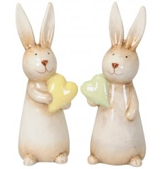 An assortment of 2 adorable bunny ornaments, each holding a yellow or green polka dot pastel heart.